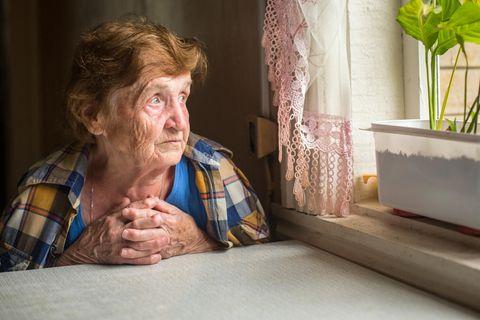 Corona aktuell: Alte Damen schaut traurig aus dem Fenster