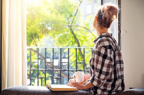 Achtsam durch die Krise: Eine junge Frau schaut aus dem Fenster