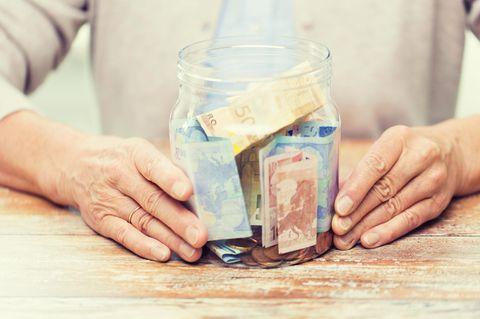 Geldanlage im Alter: Ältere Frau mit Geldglas in den Händen