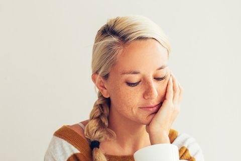 Nicht beziehungsfähig: Frau sitzt traurig mit Tasse in der Hand im Bett