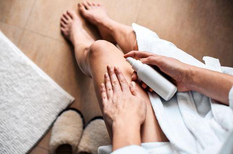 Cellulite-Creme: Frau cremt sich die Beine ein