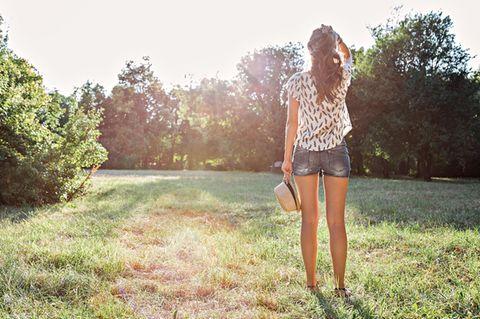 Tipps, wie du nach der Krise deine Kraft wiederfindest: Eine junge Frau von hinten in einem Park