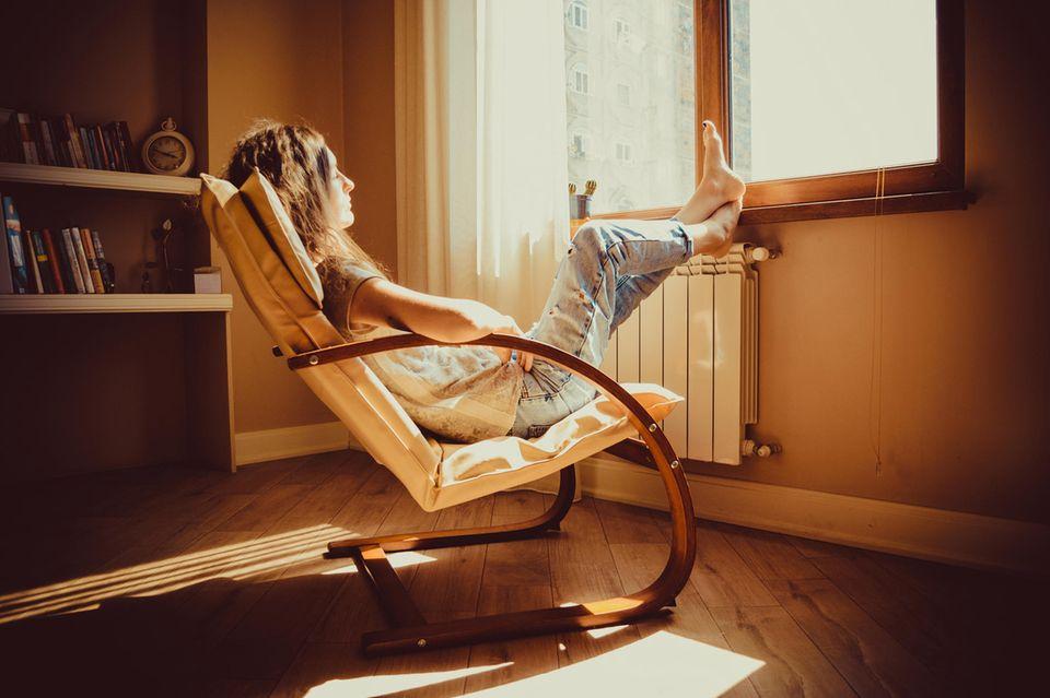 Singles in der Coronakrise: Eine Frau sitzt zu Hause auf einem Liegestuhl