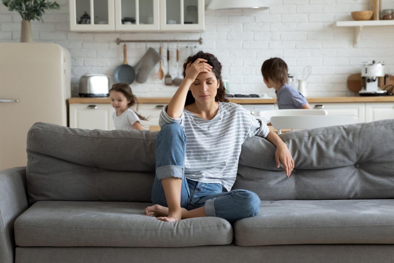 Corona-Lügen: Eine genervte Mutter sitzt auf der Couch, während ihre Kinder hinter ihr toben