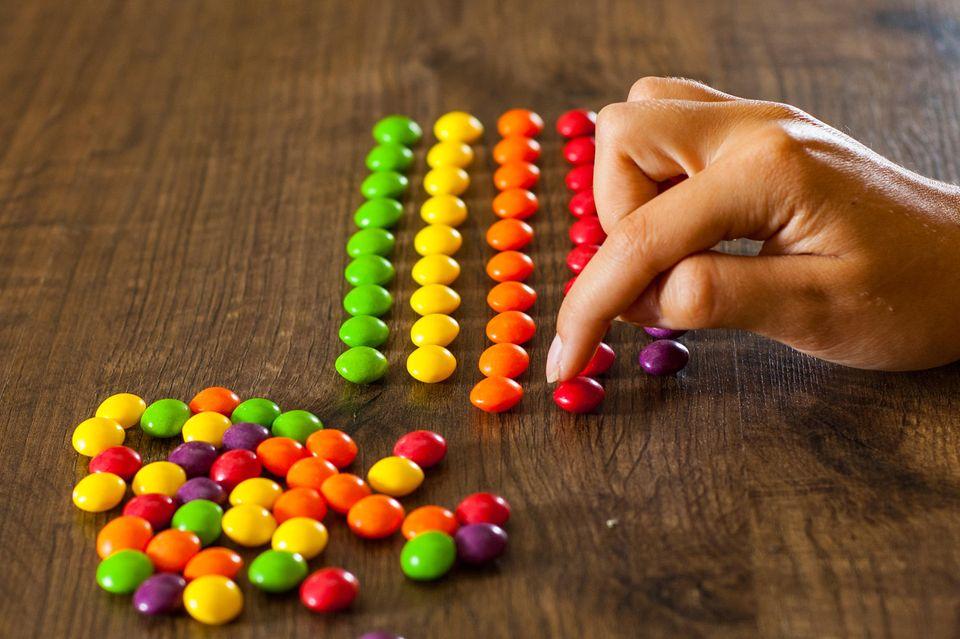 Perfektionismus: Eine Frau sortiert Schokolinsen nach Farbe