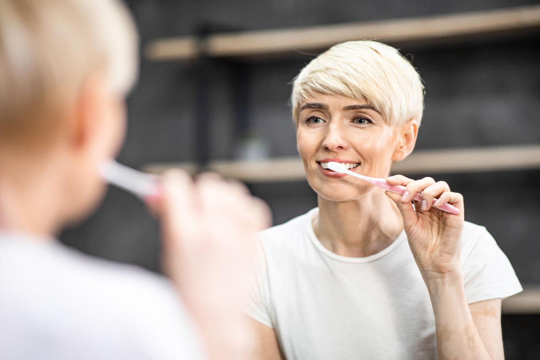 Zahnpflege in den Wechseljahren: Frau putzt sich die Zähne