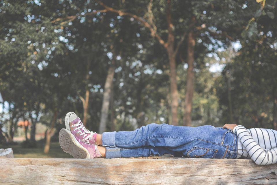 Zeit allein: Frau liegt allein in der Natur