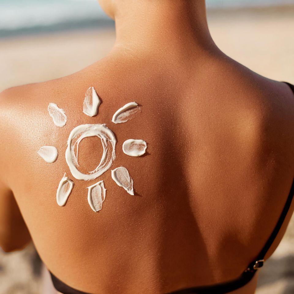 Sonnencreme-Fehler: Frau mit Sonnencreme auf dem Rücken