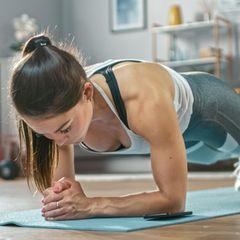 Krafttraining zu Hause: Plank, junge Frau, Home-Workout, Fitness zu Hause