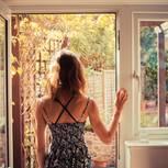 Alleine glücklich sein: Frau schaut aus Fenster