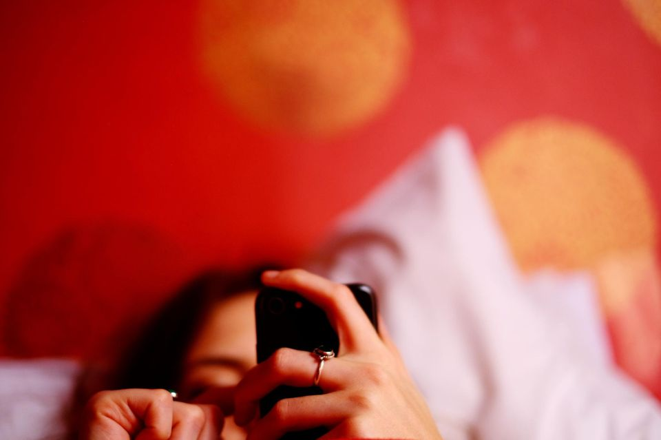Frau im Bett mit Handy