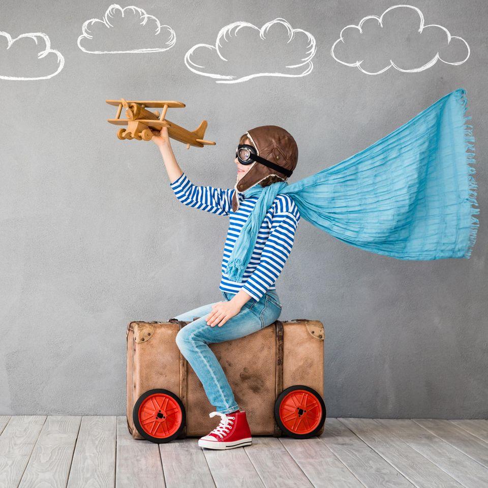 Spiele selber machen: Junge spielt mit Flugzeug