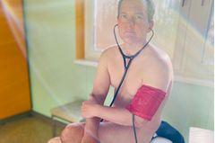 Corona aktuell: Ein unbekleideter Arzt mit Stethoskop und Blutdruckmessgerät