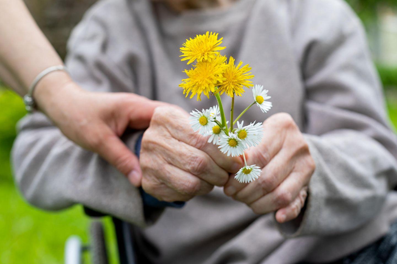 Demenz im Alter: Blumen in den Händen eines älteren Menschen