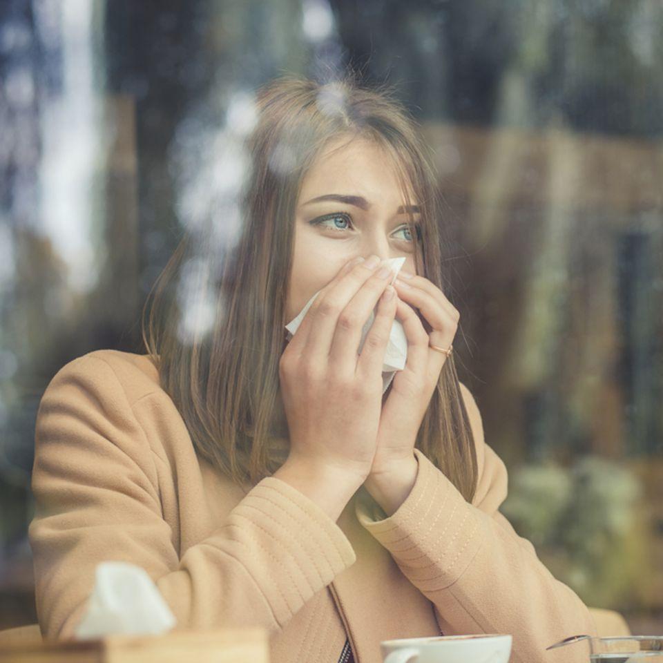 Allergischer Schnupfen: Frau putzt sich die Nase