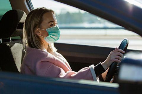 Corona aktuell: Eine Frau am Steuer eines Autos mit einem Mundschutz