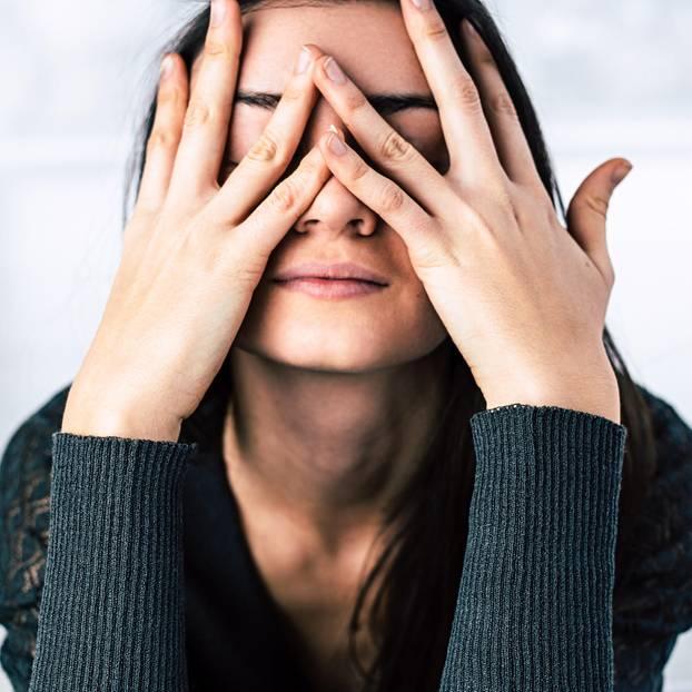 Welche Probleme haben Kontrollfreaks? Eine Frau bedeckt sich ihr Gesicht