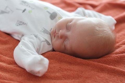 Baby auf rotem Handtuch