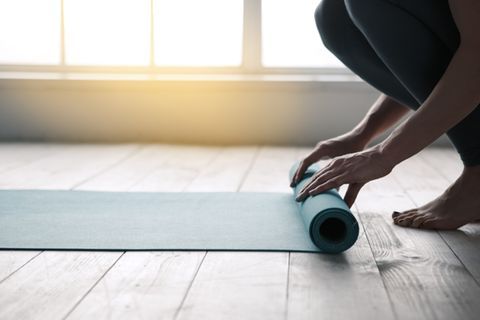 Yoga nach dem Aufwachen: Frau rollt Yogamatte aus