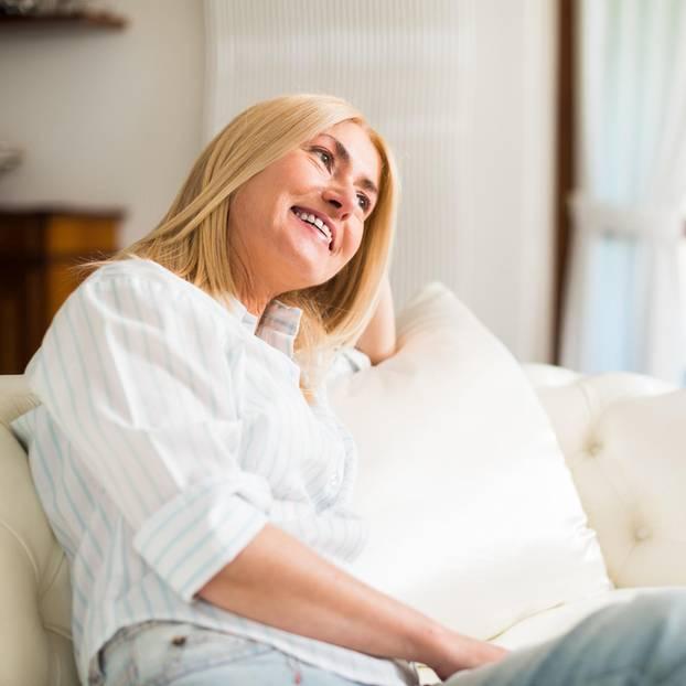 Älter werden: Frau auf weißem Sofa