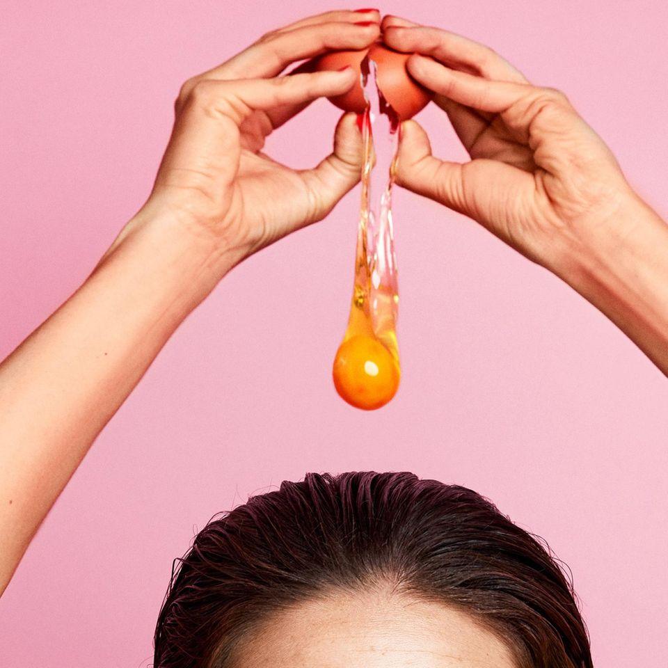 Haare pflegen: Salon-Treatments im Test: Frau schlägt Ei über ihrem Kopf auf