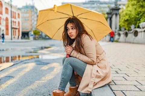 Corona aktuell: Eine nachdenkliche Frau unter einem Schirm