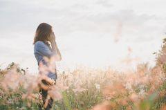 Wie verändern toxische Beziehungen den Charakter? Eine traurige Frau auf einem Feld