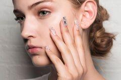 Glasnägel: Frau mit glitzernden Fingernägeln