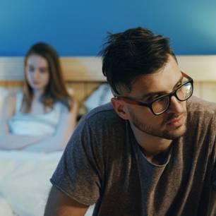 Whisper: Ein Mann wendet sich von seiner Freundin im Bett ab