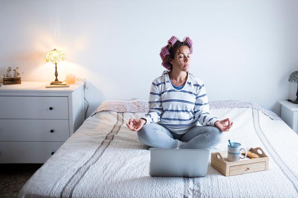 Frau auf Bett mit Laptop und Lockenwicklern