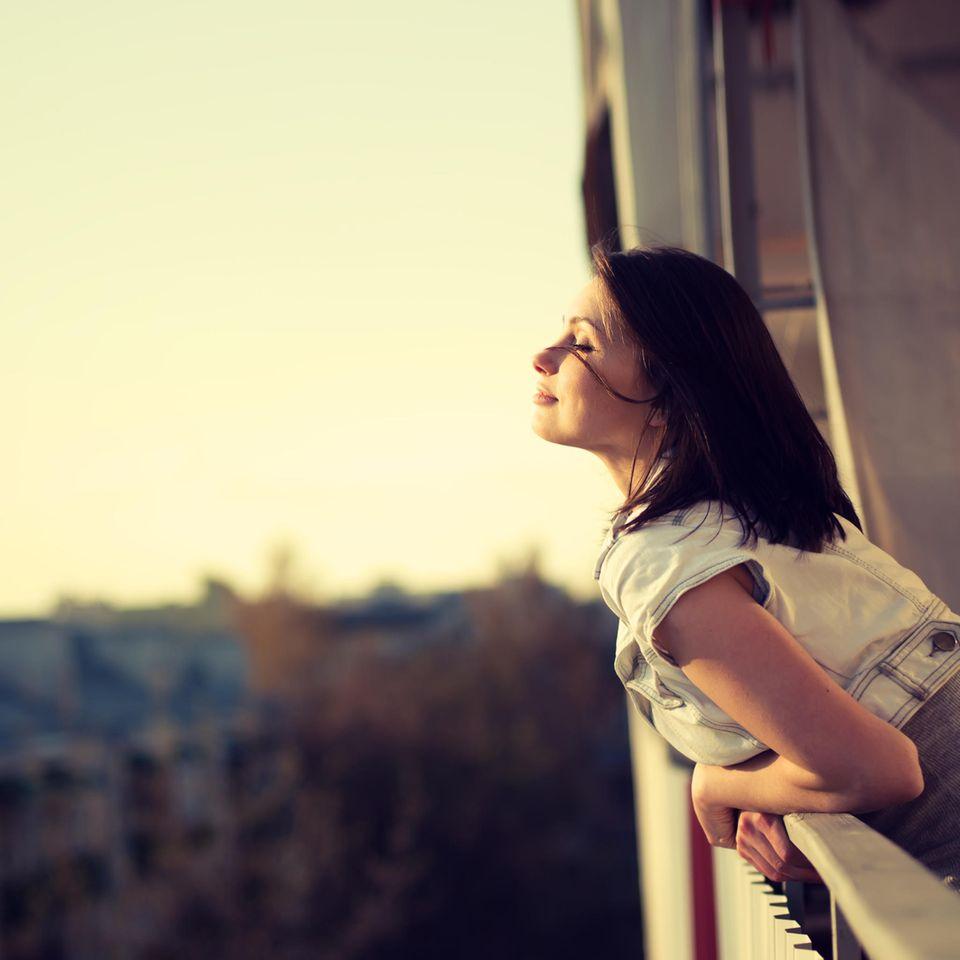 Welche Gedanken helfen gegen Angst? Eine Frau lehnt sich aus dem Fenster und genießt die Luft