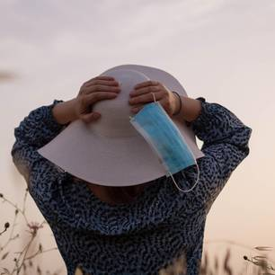 Maske richtig transportieren: Frau mit Hut hält Maske in der rechten Hand