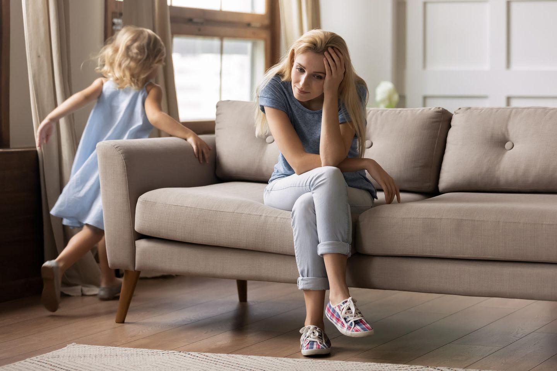 Studie: Eine erschöpfte Mutter sitzt auf der Couch, ihre Tochter läuft um sie rum