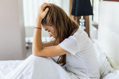 Warum kann ich keine Grenzen setzen? Eine junge, erschöpfte Frau sitzt in ihrem Bett