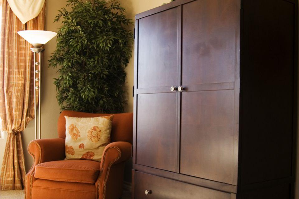 Fernseher verstecken: Wohnzimmer mit Sessel und Schrank