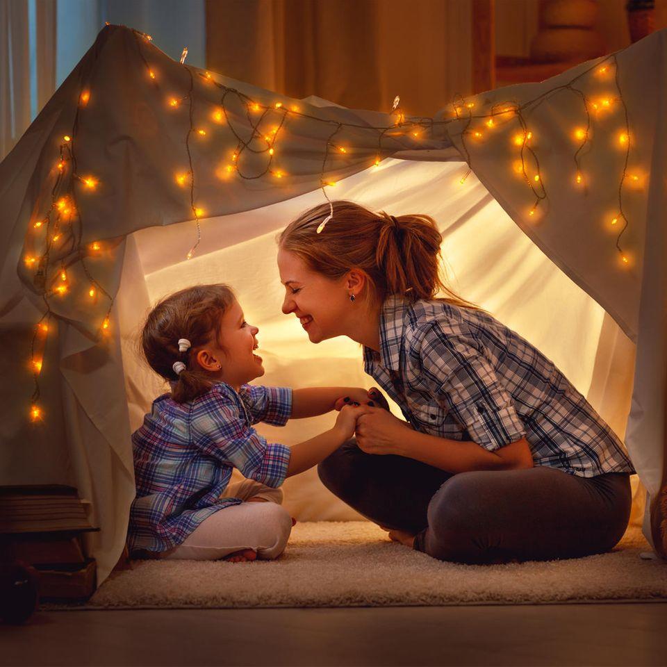 Was kann dem Selbstvertrauen von Kindern schaden? Eine Mutter mit ihrer Tochter in einem Zelt im Wohnzimmer