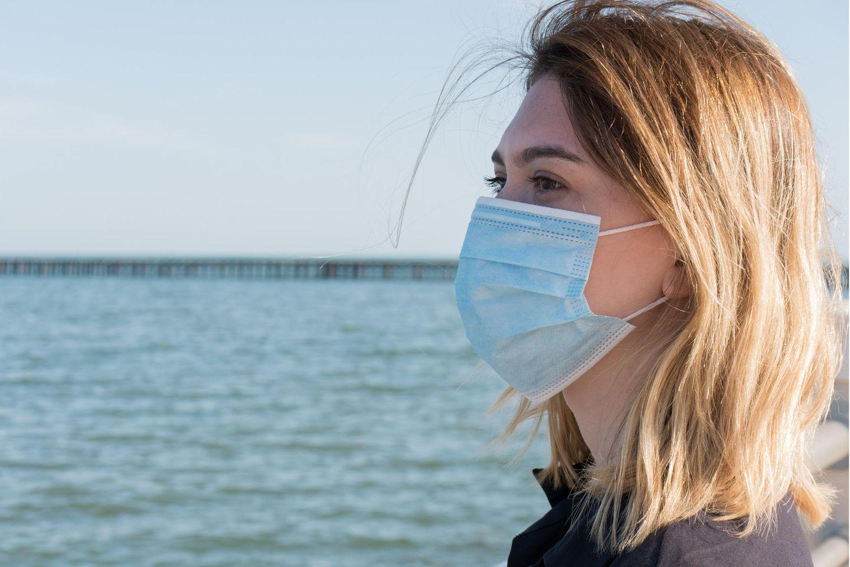Corona aktuell: Frau mit Maske am Meer
