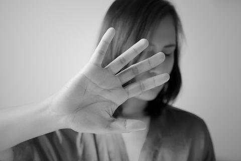 Gewalt gegen Frauen: Frau hält abweisend die Hand in die Kamera