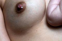 Milk: Nahaufnahme einer Brust mit Milchtropfen