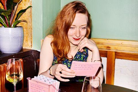 36 Fragen zum Verlieben: Frau liest Karteikarte an Tisch