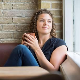 Welche Gewohnheiten machen das Leben unnötig schwer? Eine nachdenkliche Frau schaut aus dem Fenster