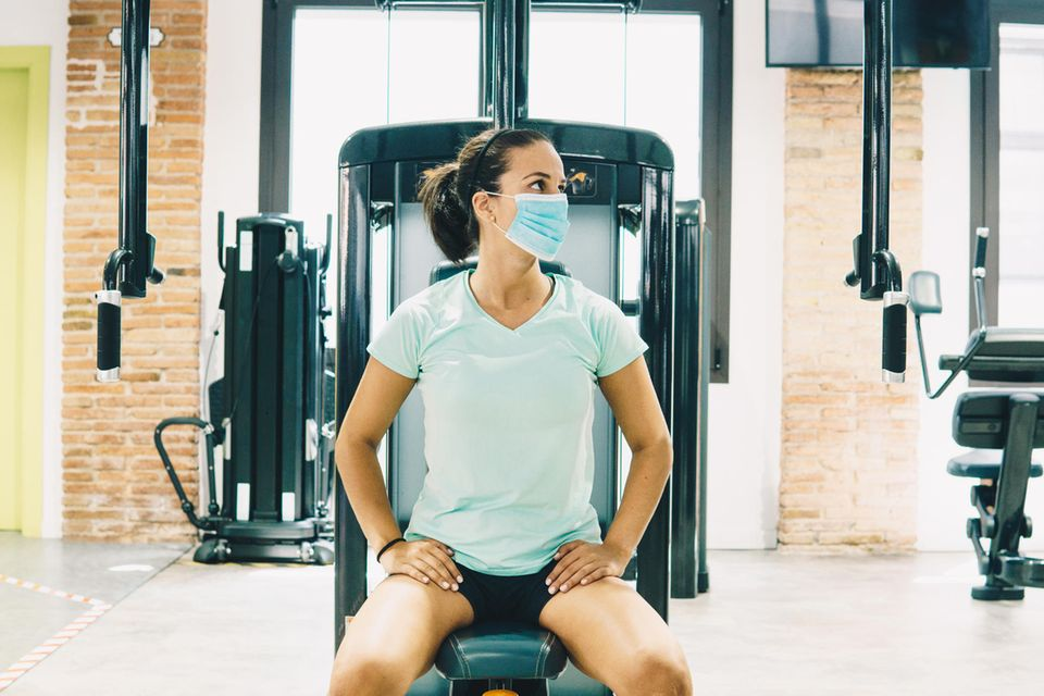Corona aktuell: Frau mit Mundschutz auf Trainingsgerät