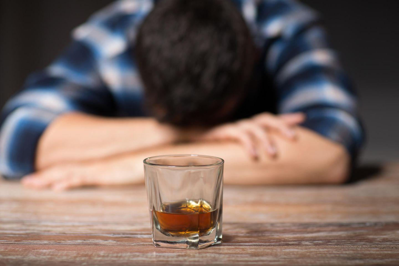 Schnapsdrossel: Mann mit Kopf auf Tisch abgelegt und Drink davor