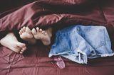 Welche Gewohnheiten schaden der Vagina? Ein Pärchen im Bett mit einem benutzten Kondom