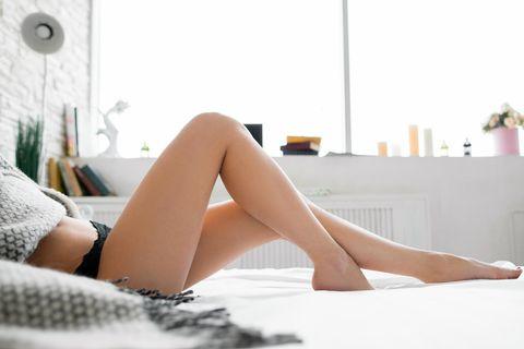 Welche Gewohnheiten schaden der Vagina? Eine Frau im Bett mit gekreuzten Beinen