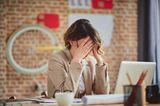 Welche Gewohnheiten schaden der Vagina? Eine gestresste Frau im Büro