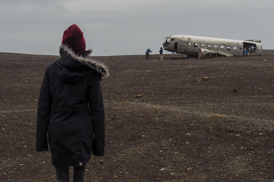 Flugzeugabsturz überlebt: Person vor abgestürztem Flugzeug