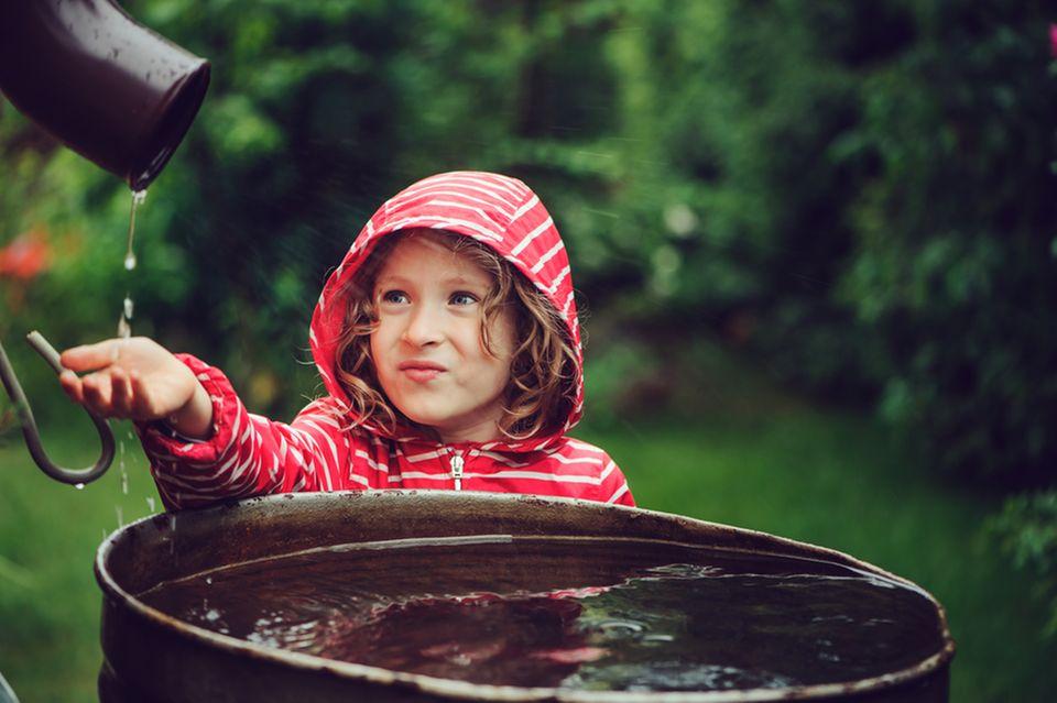Nachhaltiger Garten: Kind vor einer vollen Regentonne