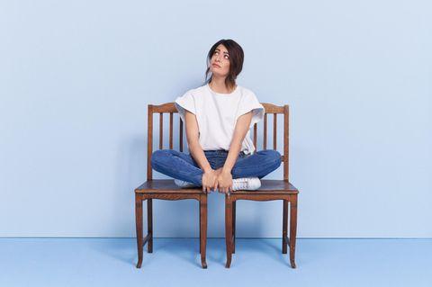 Linda Zervakis auf Stühlen sitzend