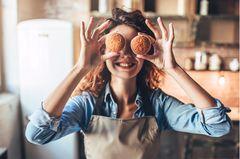 Backen ohne Zucker: Frau hält sich Muffins und lacht
